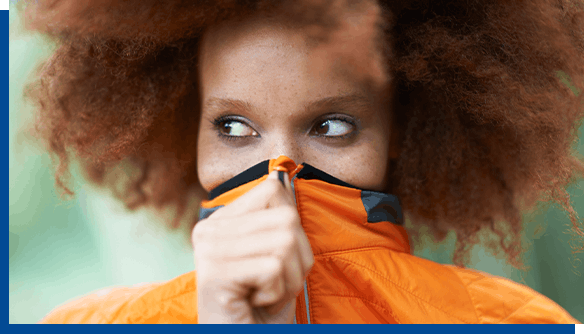 Woman in orange coat covering her face due to cold sores