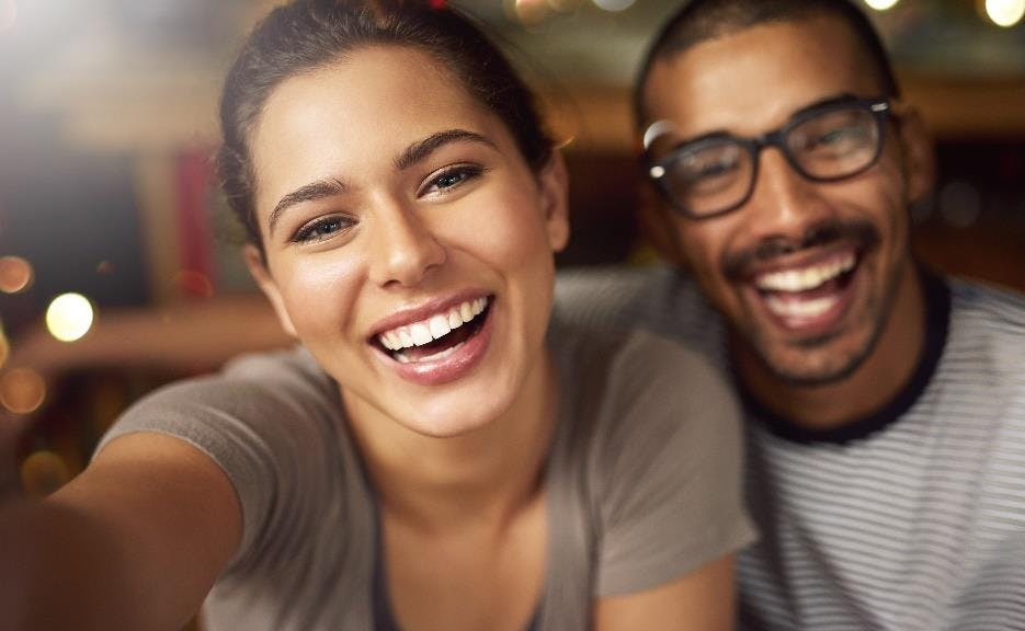 man and women smiling widely showing their teeth