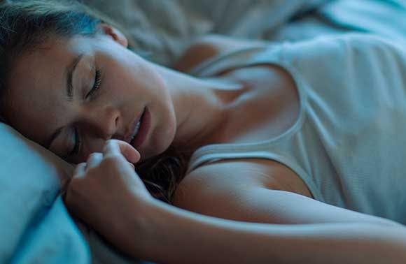 Jeune femme endormie dans son lit