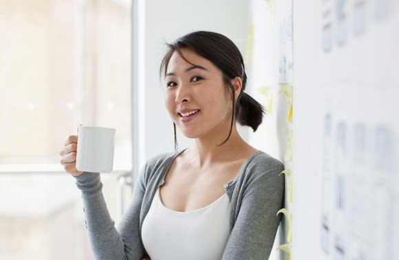 Une femme souriante, tenant une tasse de café