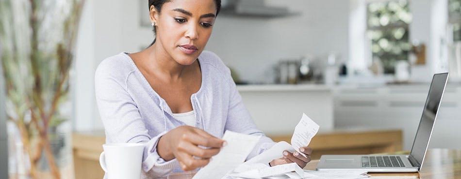 Femme examinant des factures | Dressez un budget