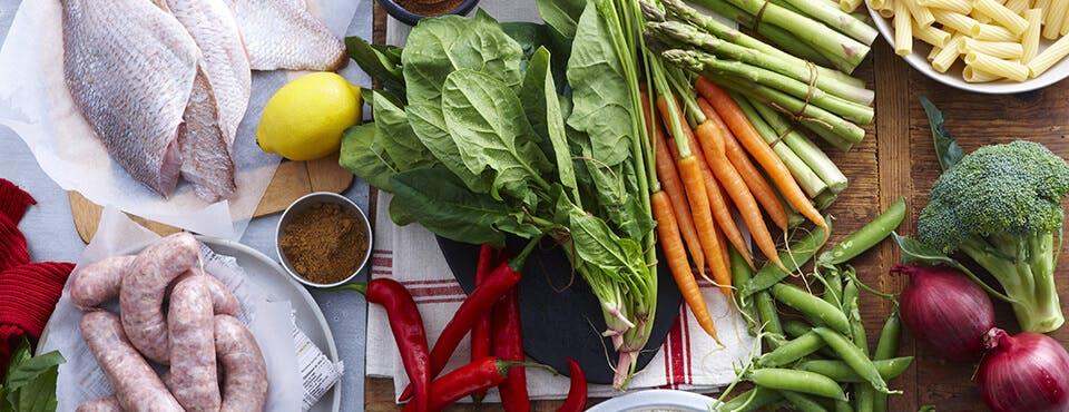 Divers légumes, saucisse et poisson crus disposés sur une table