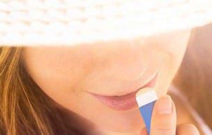Une femme appliquant un baume pour les lèvres