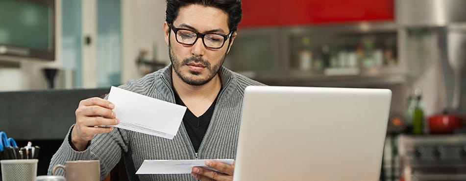 Homme lisant le courrier | Révisez votre budget chaque mois