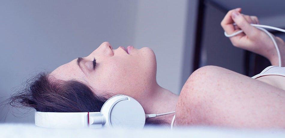 Femme qui écoute de la musique les yeux fermés   Adoptez un rituel avant de vous coucher