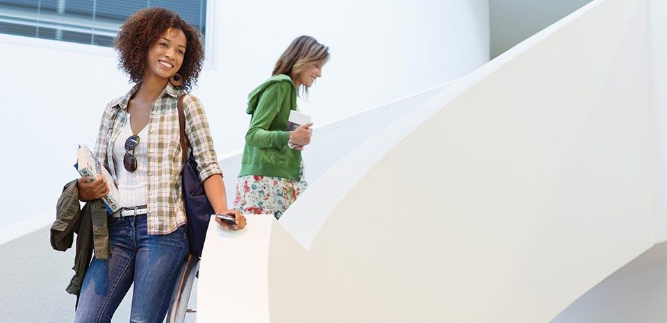Femme souriante dans un escalier   Allez-y à pied