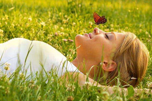 Une femme étendue dans l'herbe, un papillon posé sur le nez