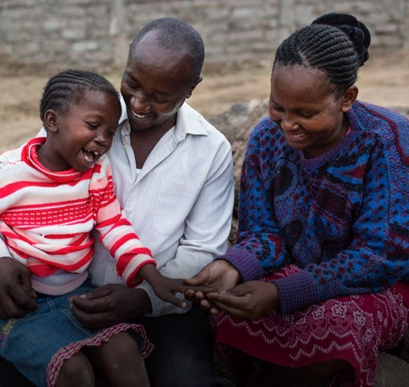 Two adults and a child post cleft surgery, all smiling