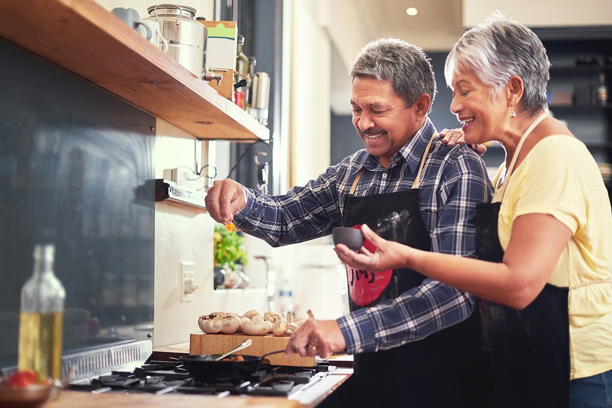 A male and female cooking together
