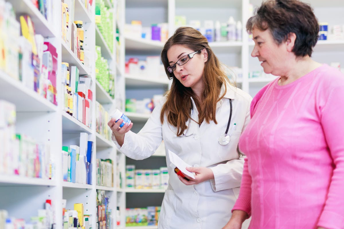Pharmacist and consumer discussing medication in pharmacy aisle