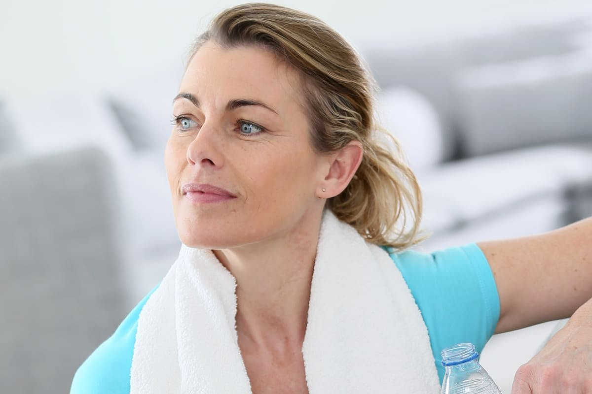 Woman sitting and resting on an exercise ball while drinking water.