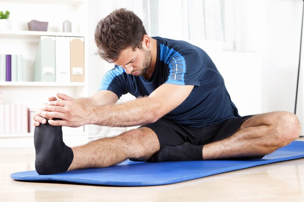 Man in his mid-thirties doing hamstring stretches on a blue yoga mat