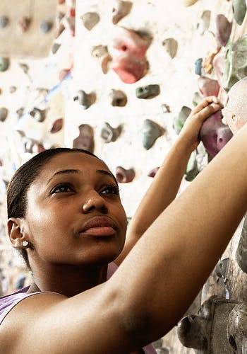 Young woman indoor rock-climbing
