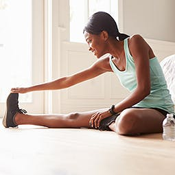 Young woman exercising and stretching her legs