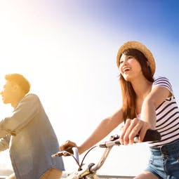 Young couple cycling and smiling