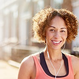 Woman smiling and listening to  music with headphones