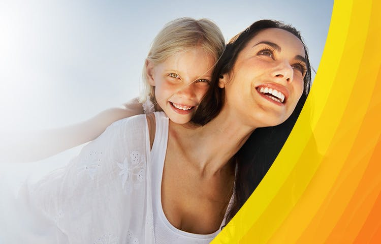 Smiling woman carrying a young girl on her back