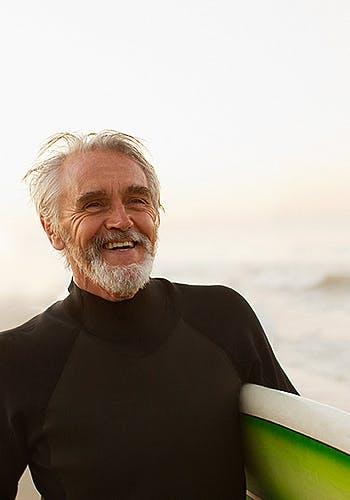 Homme âgé combinaison de plongée tenant une planche de surf