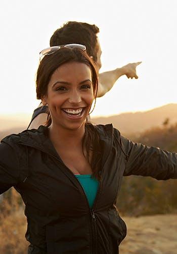 Femme souriante et un homme derrière elle pointant vers une autre direction