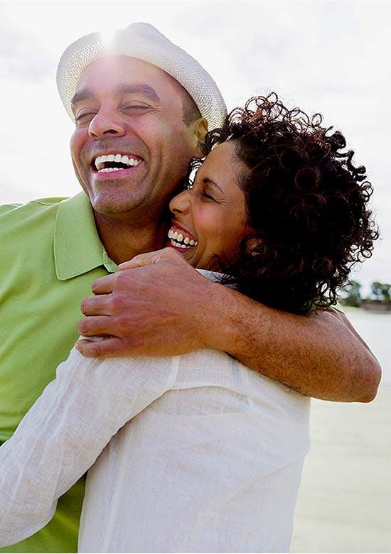 Heureux couple souriant et se tenant sur une plage