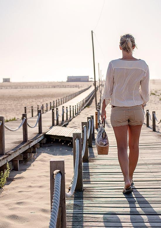 Jeune femme marchant sur une promenade sur la plage