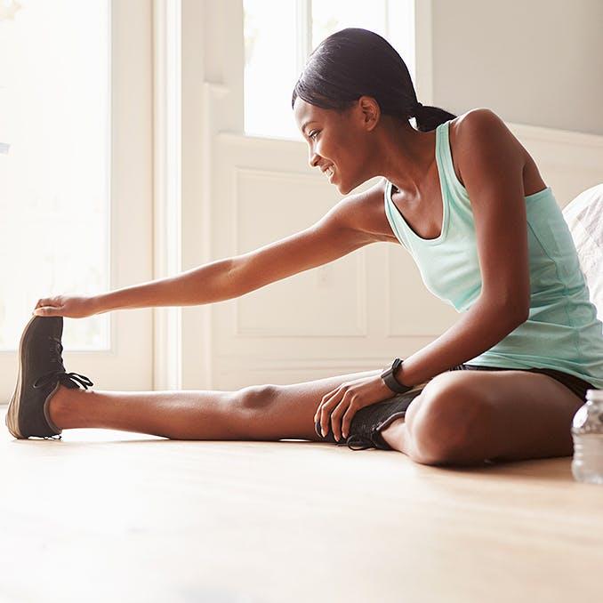 Jeune femme exerçant et étirant ses jambes