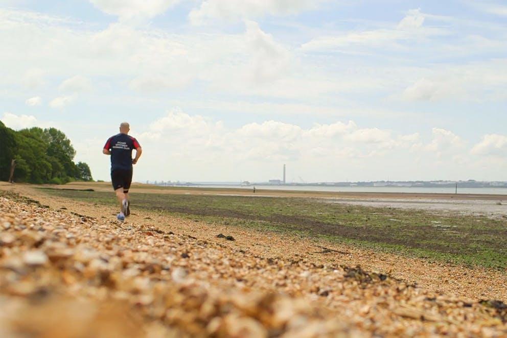 Homme qui fait du jogging sur une plage