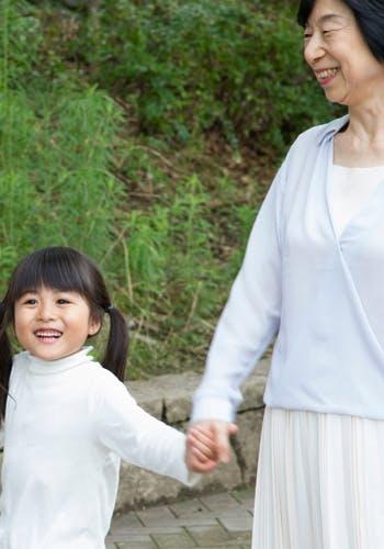 手を繋いで歩く2人の女性と幼い女の子