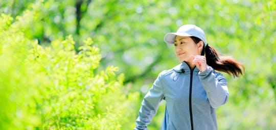 新緑の中をジョギングする女性