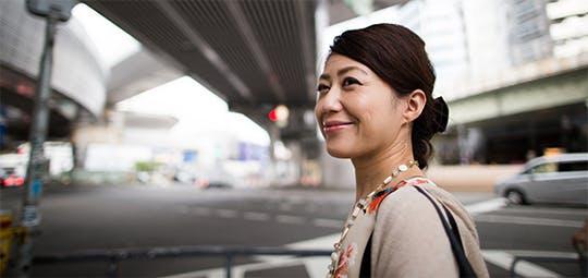 高架下を笑顔で歩く女性