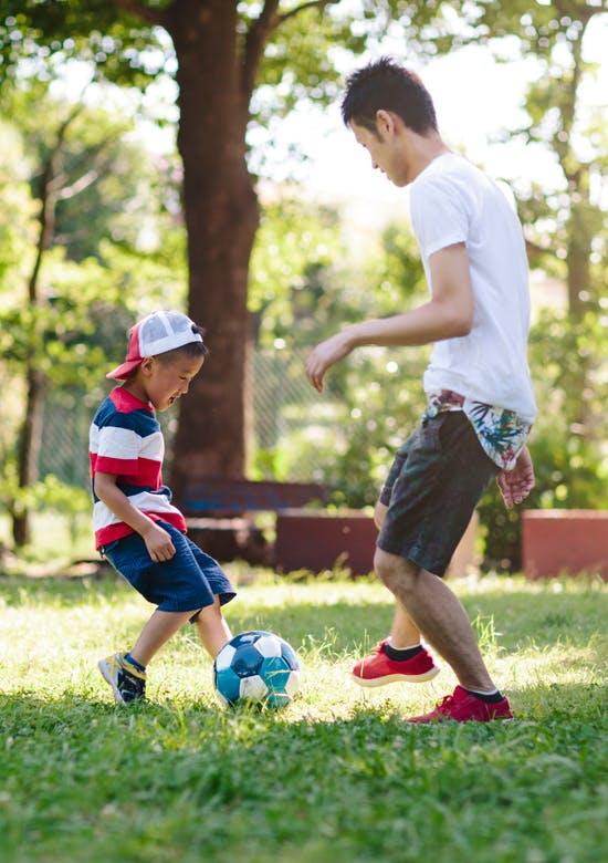 公園でボールを蹴る男の子と男性