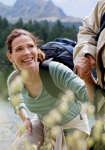 Leki przeciwbólowe - uśmiechnięta kobieta z plecakiem wstaje poczas wycieczki w górach