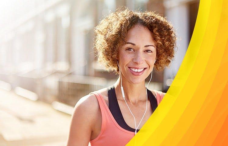 Uśmiechnięta kobieta w kręconych włosach z białymi słuchawkami