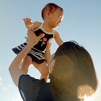 Jak działa Voltaren, aby zmniejszyć ból? Kobieta podnosi dziecko na tle nieba.