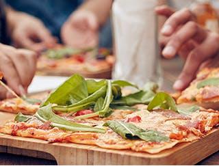 Plusieurs personnes partageant une pizza à croûte mince