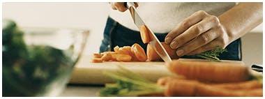 Femme coupant des carottes sur une planche à découper