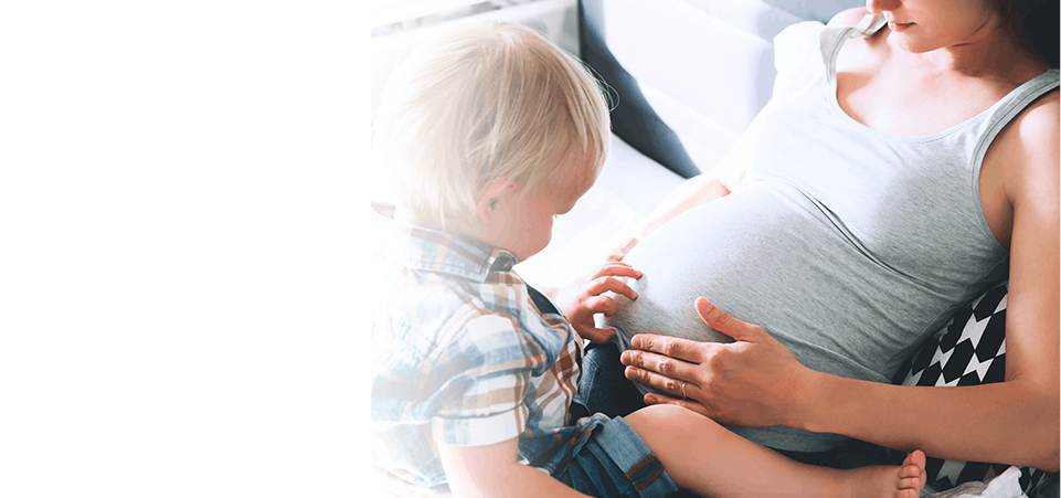 Femme enceinte avec son bambin sur les genoux