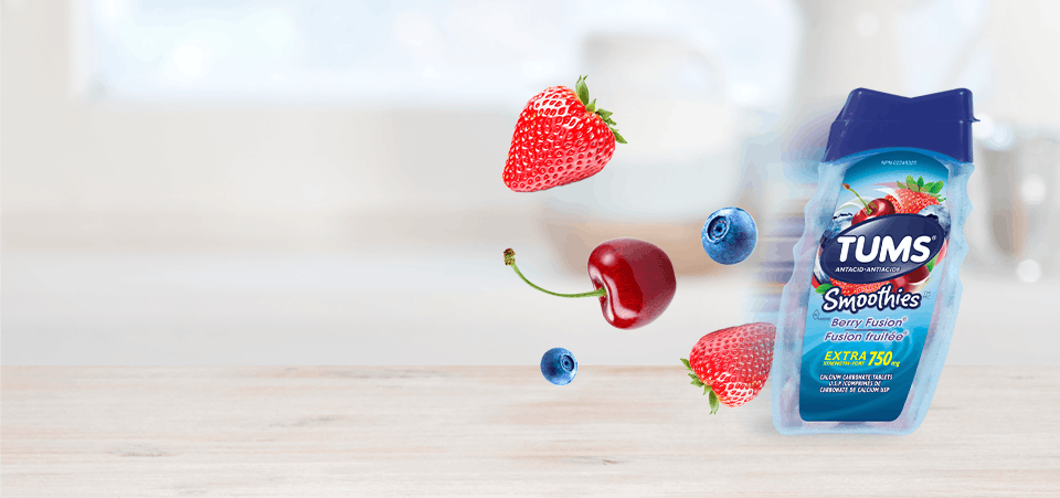 Bottle of Tums smoothies with cherries, blueberries and strawberries behind it