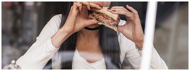 Jeune femme mangeant un sandwich santé