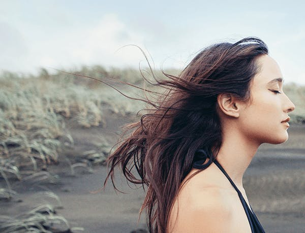 Woman closing her eyes with wind in her hair