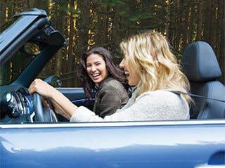 To unge kvinner i cabriolet som ler og smiler